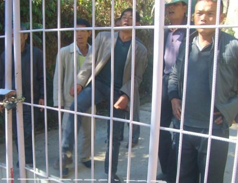 門を蹴って脅す男たち