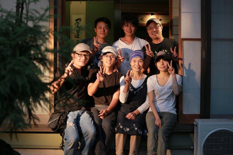 えいこばあちゃんと記念写真を撮る撮影スタッフとあーちゃん(前列左から2人目)
